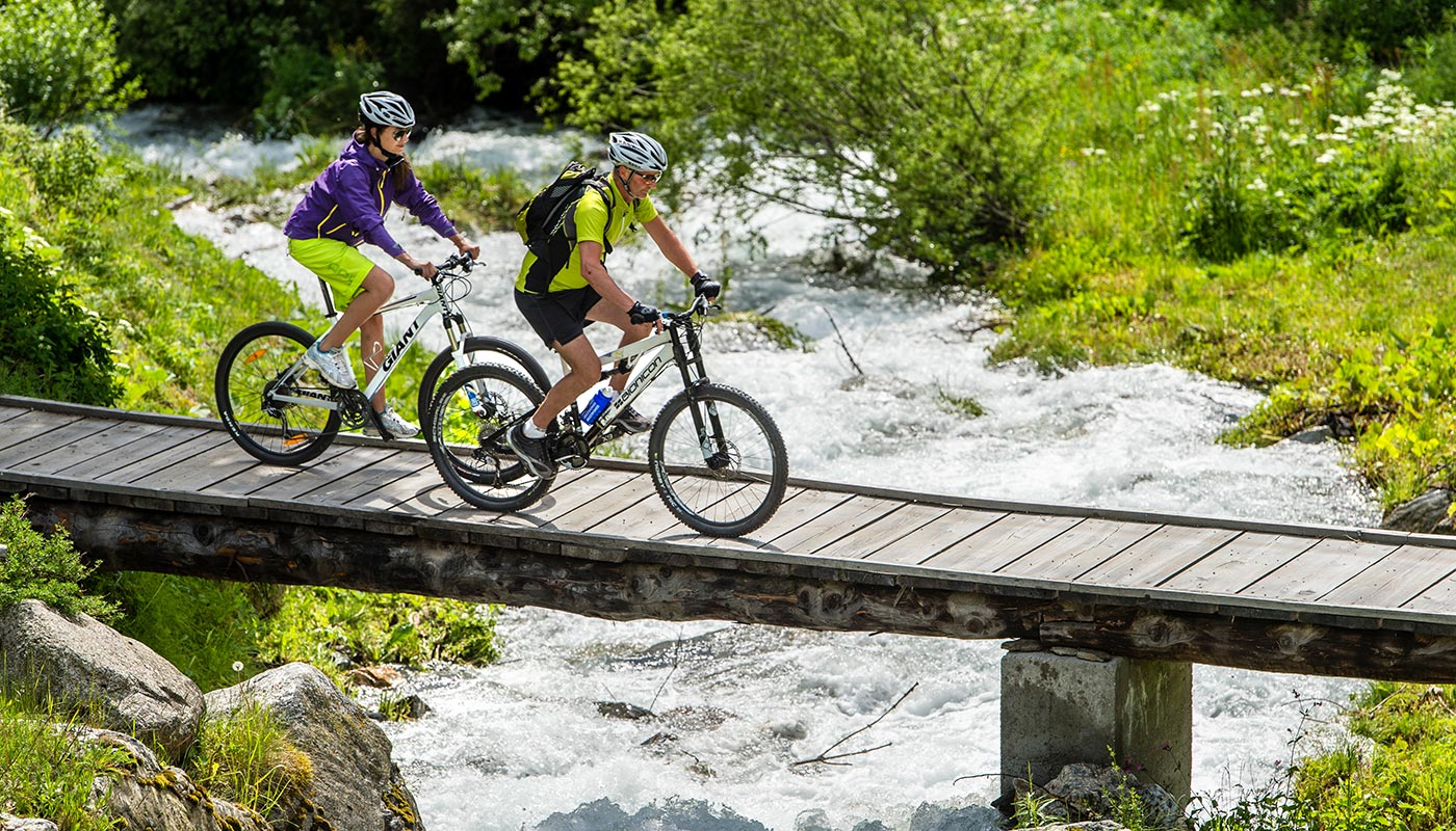 two people are crossing a wooden bridge on their mountainbikes in Pustertal near Kronplatz