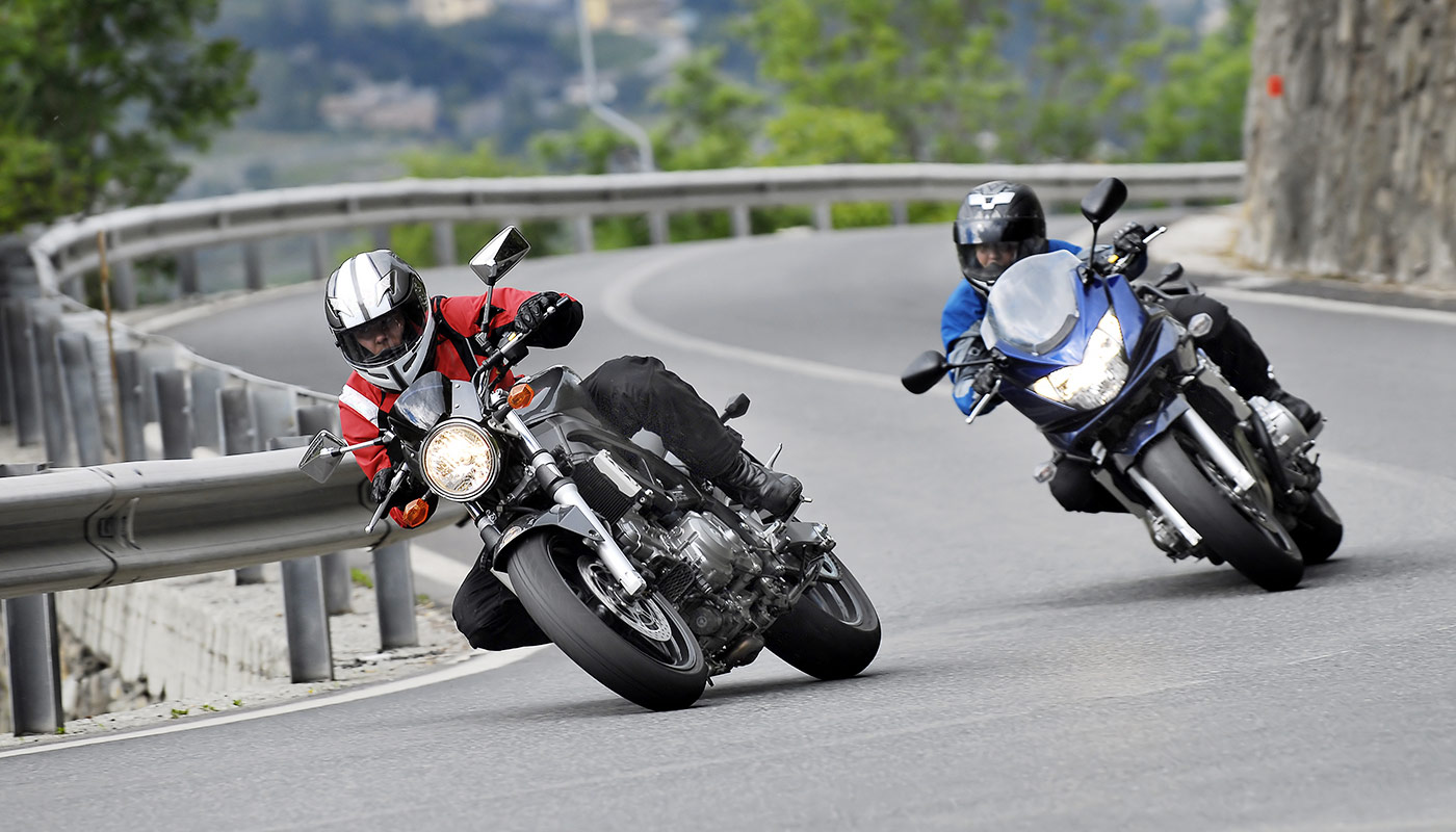 two motorcyclists are driving their motorbikes on the street in a curve