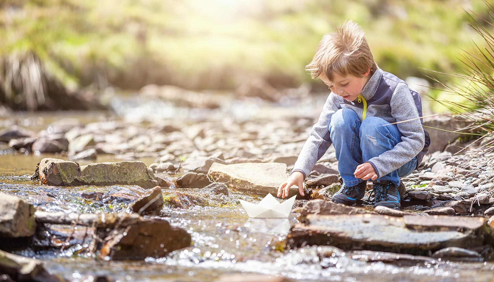 a small child lets a paper ship sail in the creek