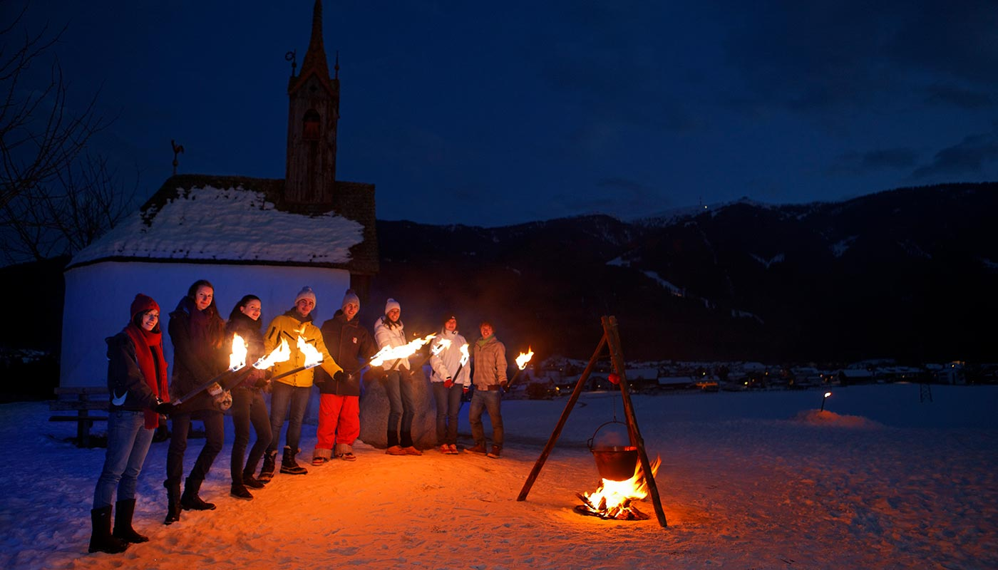 A group of tourists during the typical torchlight hike on the snow in Bruneck