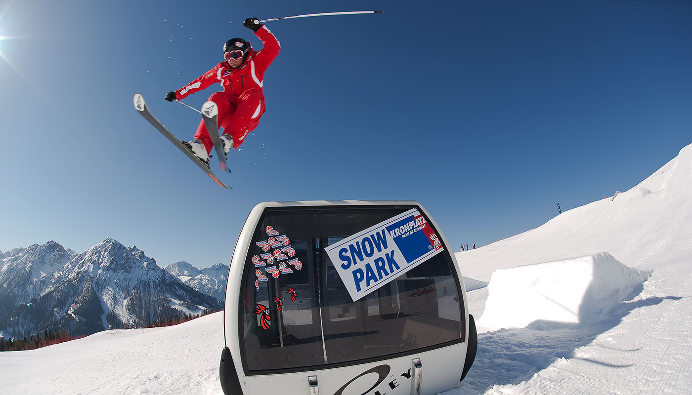 a freestyle skier jumps over a cable car in the snowpark at Kronplatz