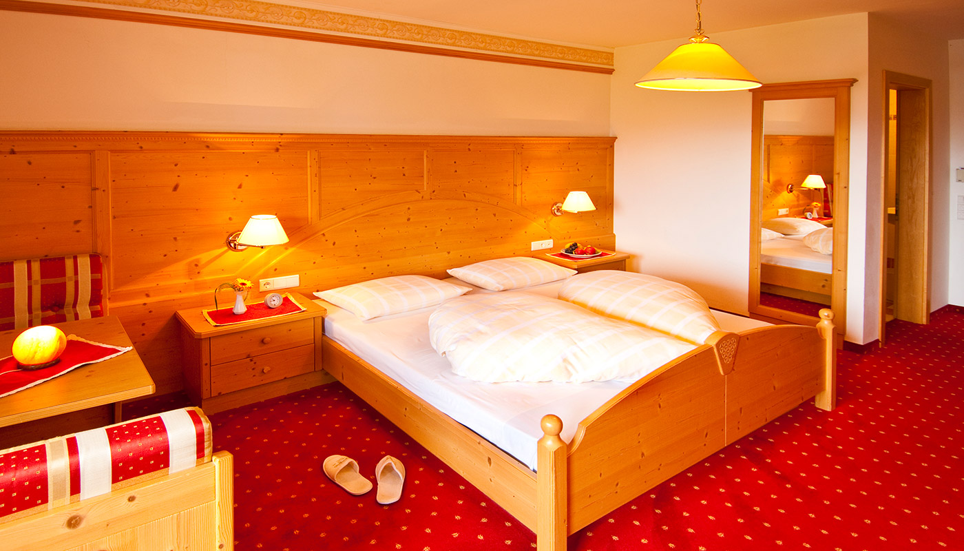 a cosy room with double bed in the Hotel Tannenhof in Reischach