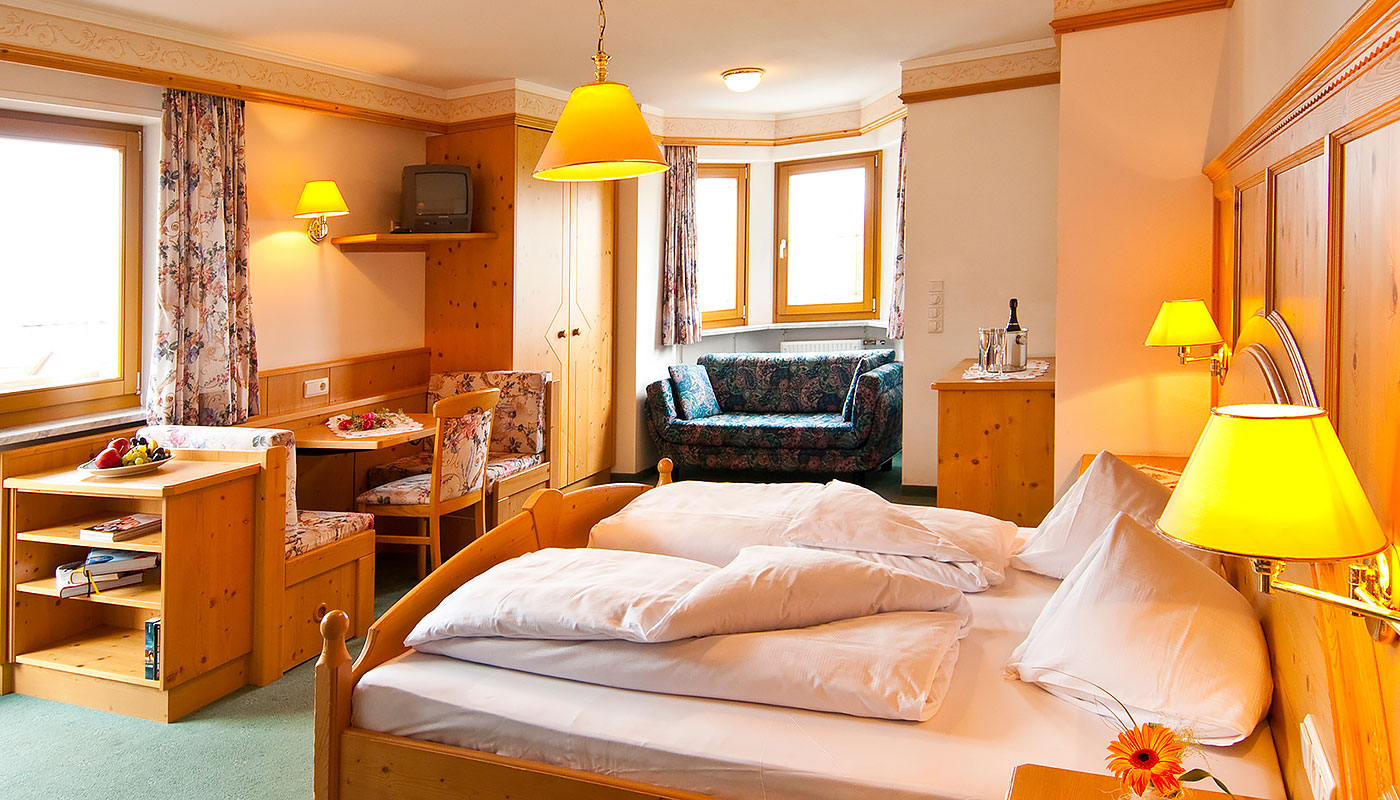 a comfortable double room of Hotel Tannenhof with wooden furniture